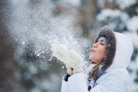 девушка сдувает снег с рук