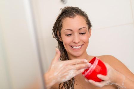 девушка в дуще моет волосы шампунем с витаминами
