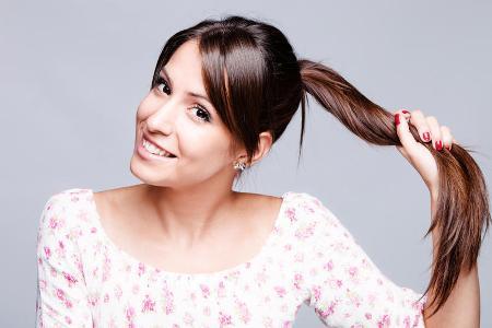 девушка показывает длину своих волос