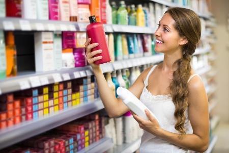 девушка с кудрявыми волосами выбирает шампунь