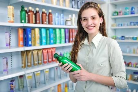 девушка в магазине выбирает шампунь