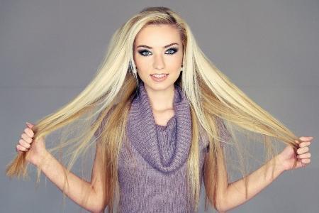 девушка показывает нарощенные волосы