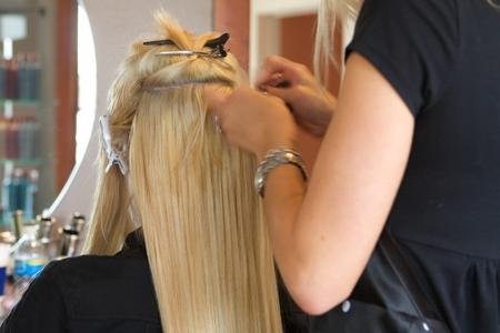 девушка на процедуре ленточного наращивания волос
