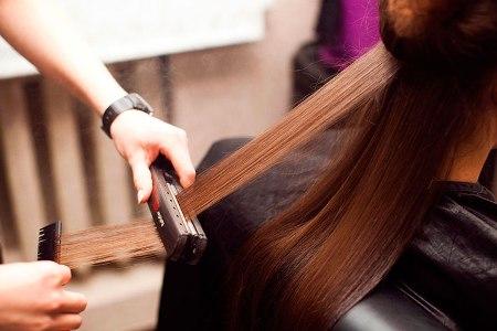 девушка на керамическом выпрямлении волос в салоне