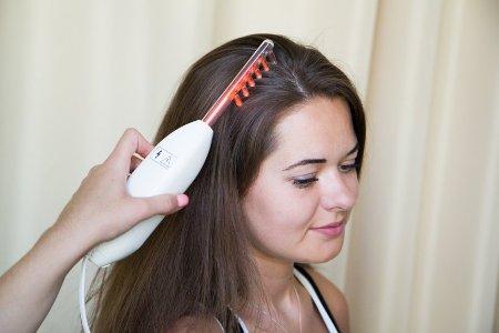 девушка проходит процедуру дарсонвализации волос